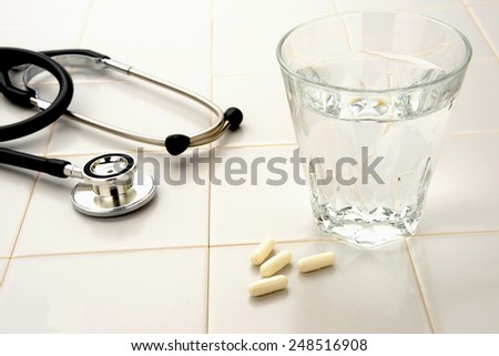 Health care concept, capsule stethoscope and cup of water - stock photo