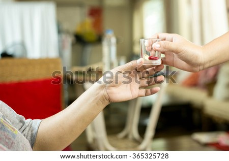 Health care Doctor giving a medicine to the patient - stock photo