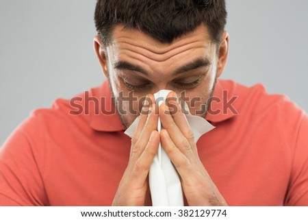 health care, flu, allergy, hygiene and people concept -sick man blowing nose to paper napkin at home - stock photo