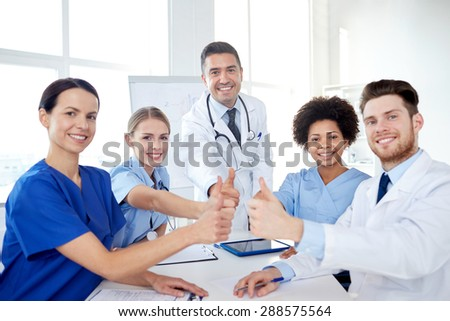 health care, medical education, people and medicine concept - group of happy doctors or interns with mentor meeting and showing thumbs up gesture at hospital - stock photo