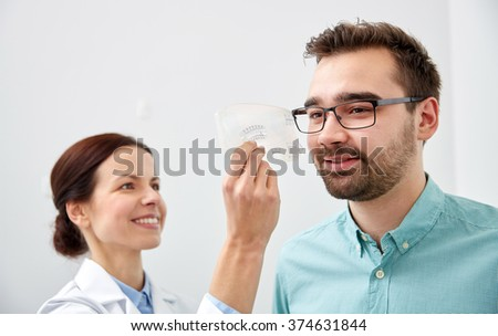 health care, medicine, people, eyesight and technology concept - optometrist with scale checking patient sight eye clinic or optics store - stock photo