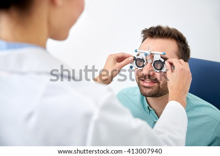 health care, medicine, people, eyesight and technology concept - optometrist with trial frame checking patient vision at eye clinic or optics store - stock photo