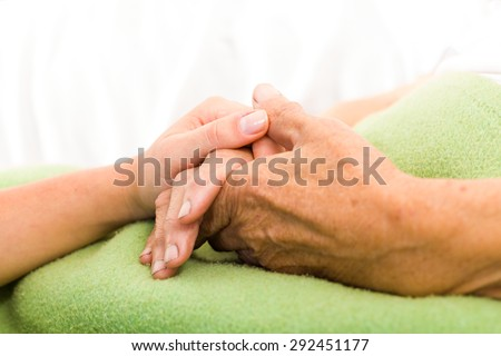 Health care nurse caring for elderly concept - holding hands.