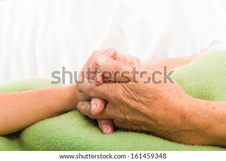 Health care nurse holding elderly lady's hand with caring attitude. - stock photo