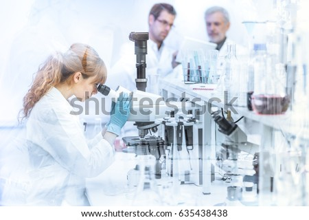 Health care researchers working in life science laboratory. Female researcher microscoping, scientists looking focused at tablet computer screen evaluating and analyzing study data.
