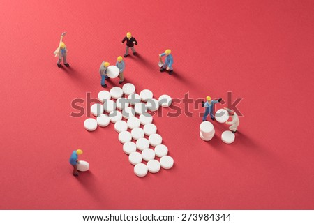 Health care system growth. Working men building a heart made of pills, symbol for medical services - stock photo