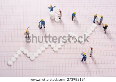Health care system growth. Working men creating medical system growth - stock photo