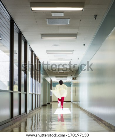 Health care worker running down a hospital corridor - stock photo