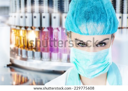 Health care worker with a mask in the front of the medical vials - stock photo