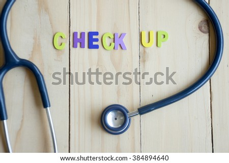 Health check up text with stethoscope on wood table - stock photo