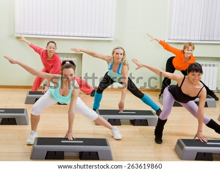 Health Club: Women of Different Age (from 18 to 50) Doing Step Aerobics in the Gym