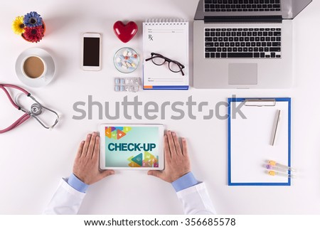 Health Concept-Doctor using tablet and showing CHECK-UP - stock photo