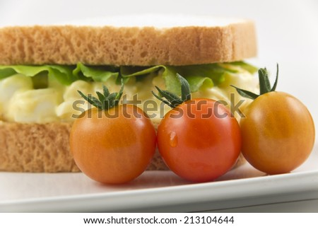 Health conscious egg salad sandwich on white bread with cherry tomatoes - stock photo