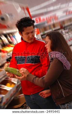 Health conscious shoppers discuss the virtues of asparagus. - stock photo