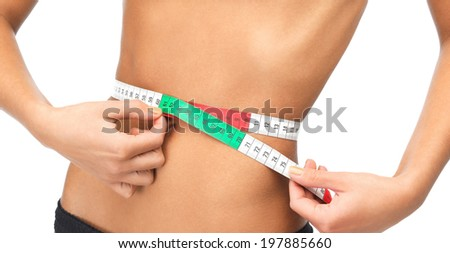 health, dieting and fitness concept - close up of woman measuring her waist with measuring tape