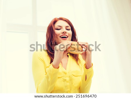 health, eating, food, home and people concept - smiling young woman eating hamburger at home - stock photo