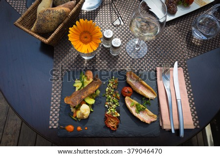 Health fish dish served at a French restaurant displayed with a French cozy table setting