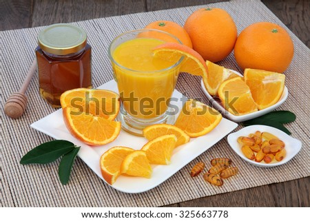 Health food for cold cure relief with freshly squeezed orange fruit juice, vitamin c tablets and honey on bamboo over oak background. - stock photo