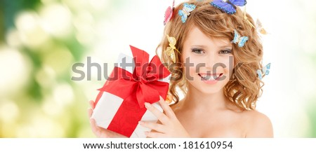 health, holidays and beauty concept - happy teenage girl with butterflies in hair showing gift box - stock photo