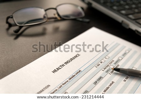 Health insurance application form on a wooden table next to laptop and glasses - stock photo