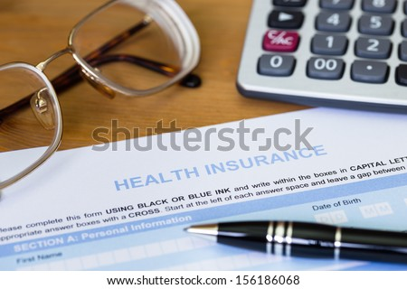 Health insurance application form with pen, calculator, and glasses - stock photo