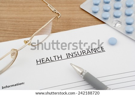 health insurance document with pills eyeglasses on wooden table - stock photo