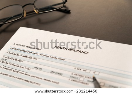 Health insurance form on a wooden table with pen and spectacles - stock photo