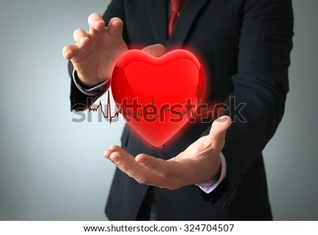 health insurance or love concept concept: hearth with electro on the hands of a businessman