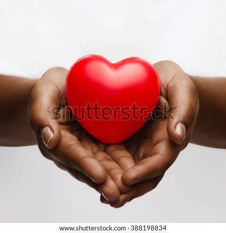 health, medicine and charity concept - close up of african american female hands with small red heart - stock photo