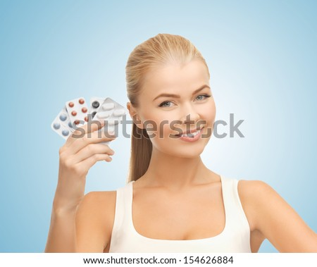 health, medicine, beauty concept - young woman with variety of pills - stock photo