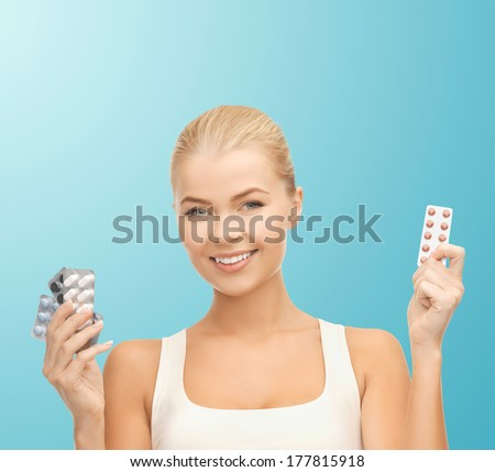 health, medicine, diet and pharmacy concept - young woman with variety of pills - stock photo