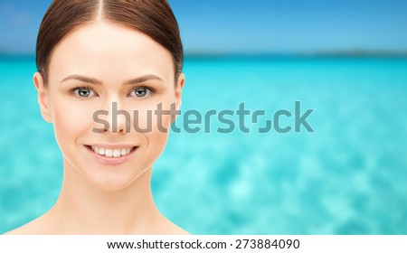health, people and beauty concept - beautiful young woman face over blue sea and sky background