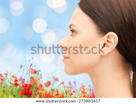 health, people and beauty concept - beautiful young woman face over poppy field background