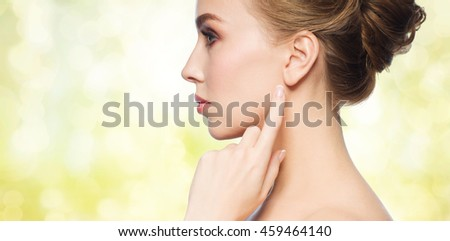 health, people and beauty concept - beautiful young woman pointing finger to her ear over yellow holidays lights background