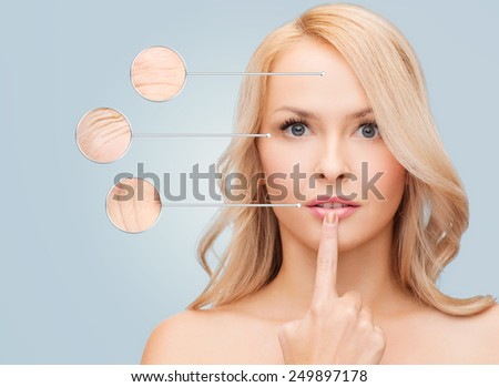 health, people and beauty concept - beautiful young woman touching her lips over blue background - stock photo