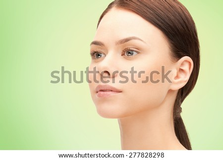 health, people, eco and beauty concept - beautiful young woman face over green background - stock photo