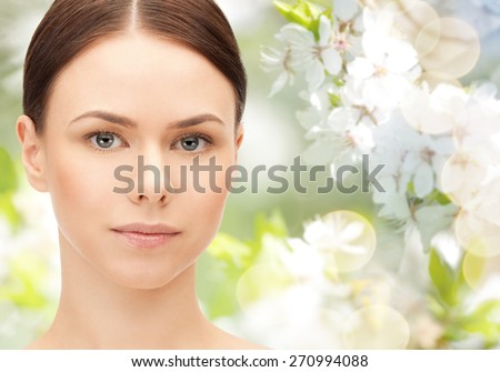 health, people, eco and beauty concept - beautiful young woman face over green blooming garden background - stock photo