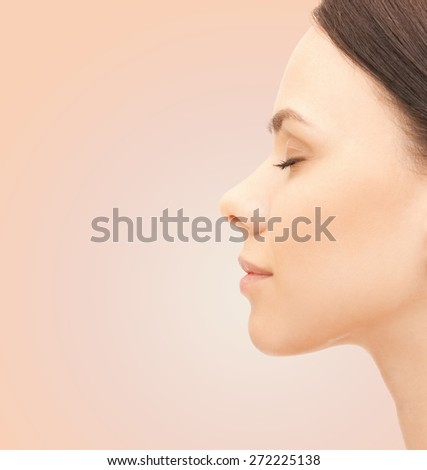 health, people, plastic surgery and beauty concept - beautiful young woman face over beige background