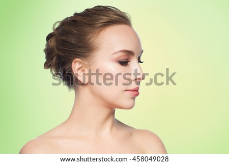 health, people, plastic surgery and beauty concept - beautiful young woman face over green background - stock photo