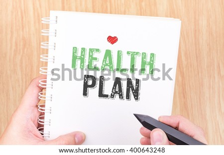 Health plan word on white ring binder notebook with hand holding - stock photo