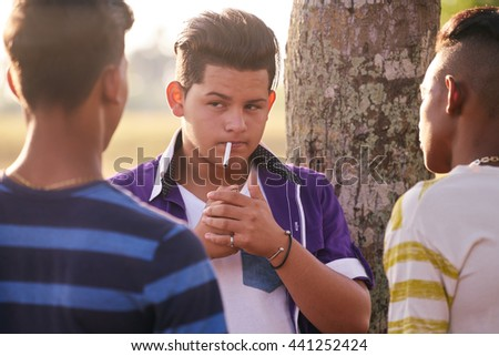 Health problems and social issues. Teenagers smoking cigarette in park. - stock photo