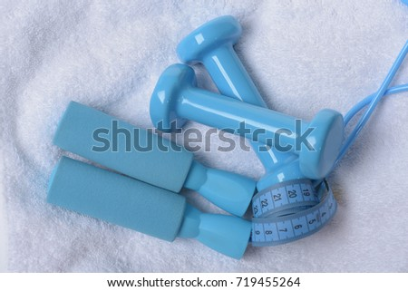 Health regime and fitness symbols. Jump rope and barbells tied with tape. Dumbbells, skipping rope and tape measure in cyan color on light soft cloth background. Healthy lifestyle and sports concept