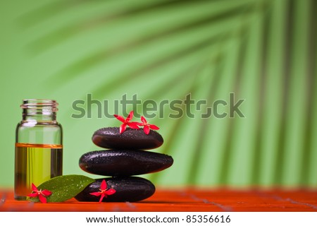 Health spa & massage still life of massage oil and balancing rocks. - stock photo