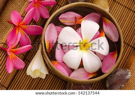 Health spa retreat setting, low light with ambient. Frangipani, hot and cold stone on bamboo mat. - stock photo