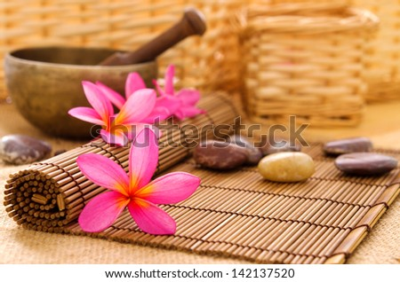 Health spa setting, low light with ambient. Frangipani, hot and cold stone on bamboo mat. - stock photo