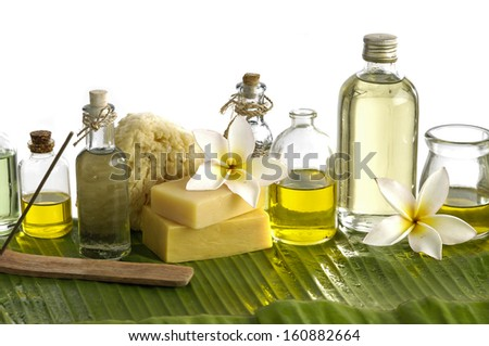 Health spa with massage oil and sunflower on leaf - stock photo