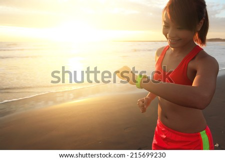 Health sport young woman run and look wear smart watch device with touchscreen on the beach at sunrise, asian - stock photo