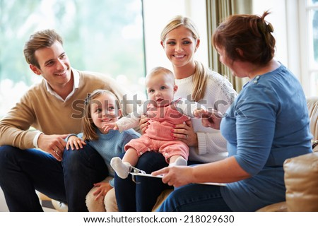 Health Visitor Talking To Family With Young Baby - stock photo