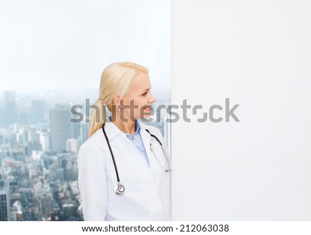 healthcare, advertisement, people and medicine concept - smiling female doctor with stethoscope looking at something over city background - stock photo