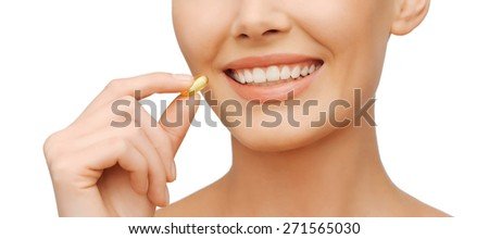 healthcare and beauty concept - beautiful woman with omega 3 vitamins